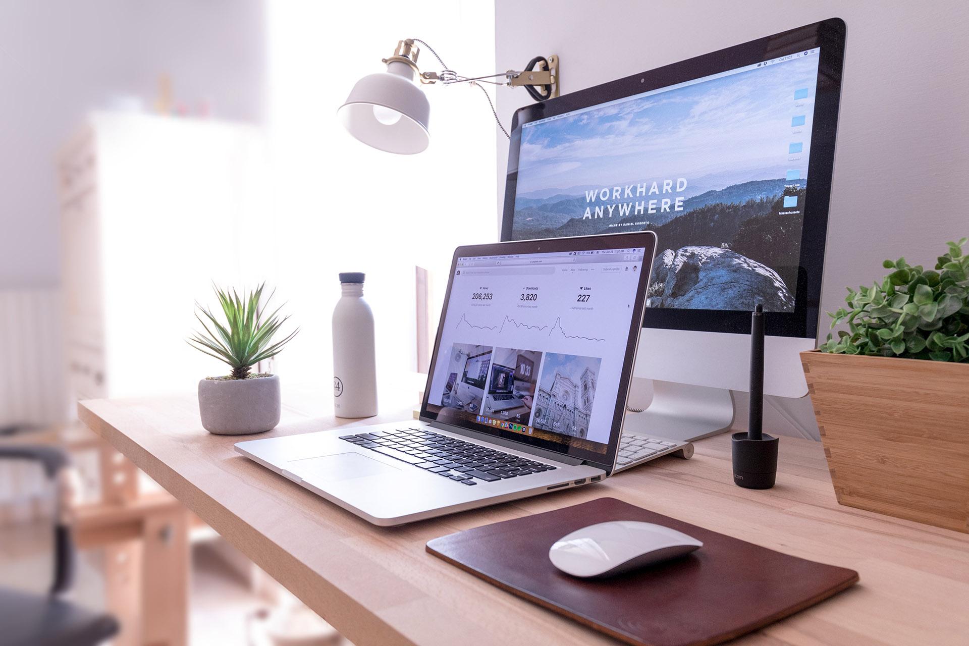 Een laptop en een beeldscherm met daarop een applicatie en een website